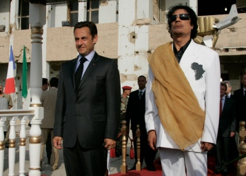 Libya's President Muammar Gaddafi (R) and his counterpart from France Nicolas Sarkozy listen to national anthems at Bab Azizia Palace in Tripoli July 25, 2007. REUTERS/Pascal Rossignol (LIBYA)